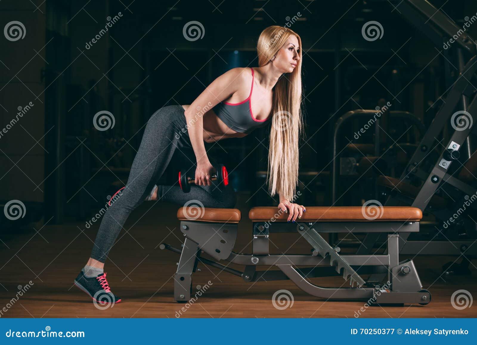 Den brutala idrotts- kvinnan som pumpar upp, tränga sig in med hantlar i idrottshall