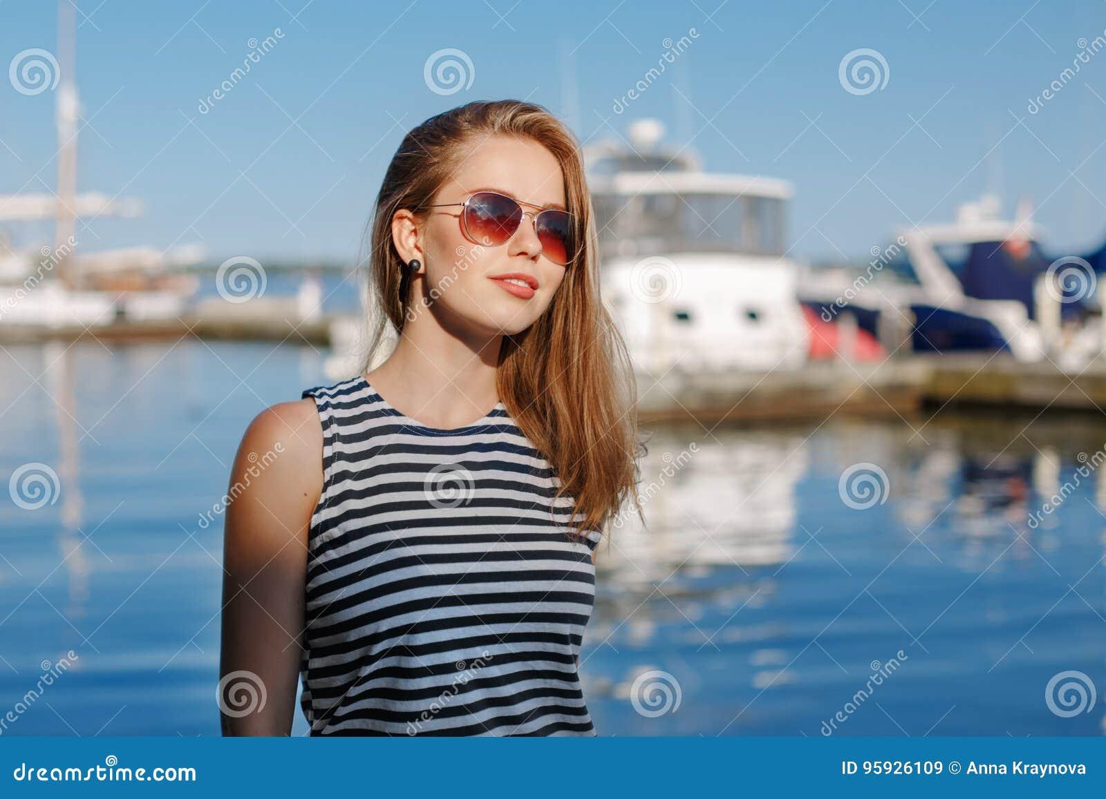 Den Caucasian blonda kvinnan med brunbränd hud gjorde randig t-skjortan och jeans vid kusten lakeshore, med yachtfartyg på bakgru