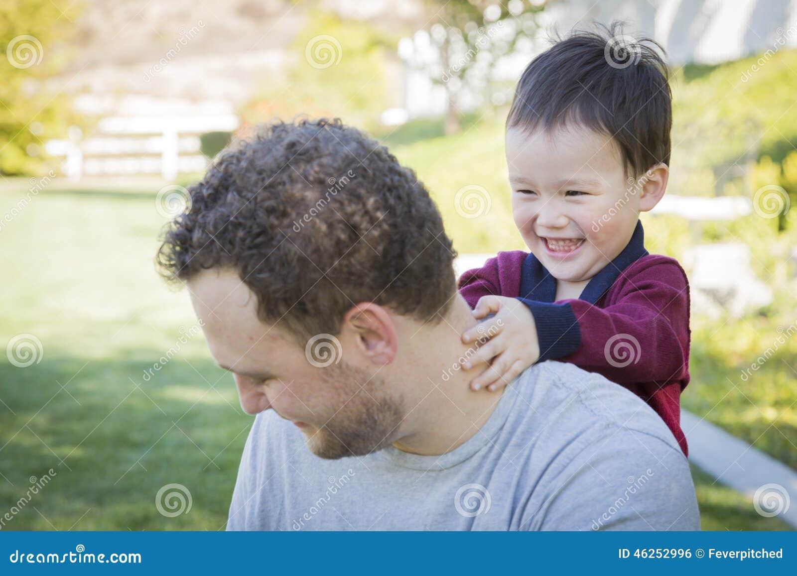 Den Caucasian fadern Having Fun med hans blandade lopp behandla som ett barn sonen