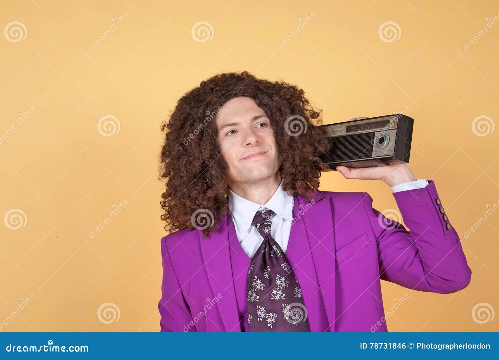 Den Caucasian mannen med afro bärande lilor passar att lyssna till musik