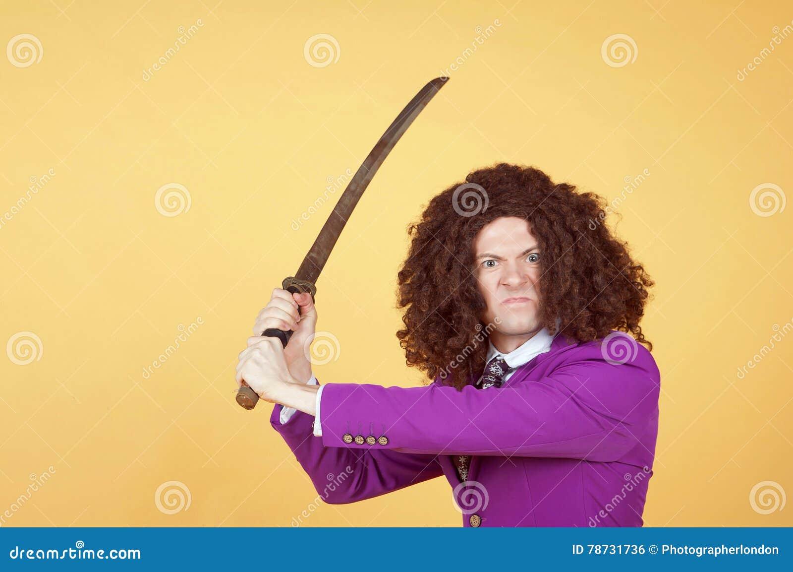 Den Caucasian mannen med afro bärande lilor passar det bärande svärdet