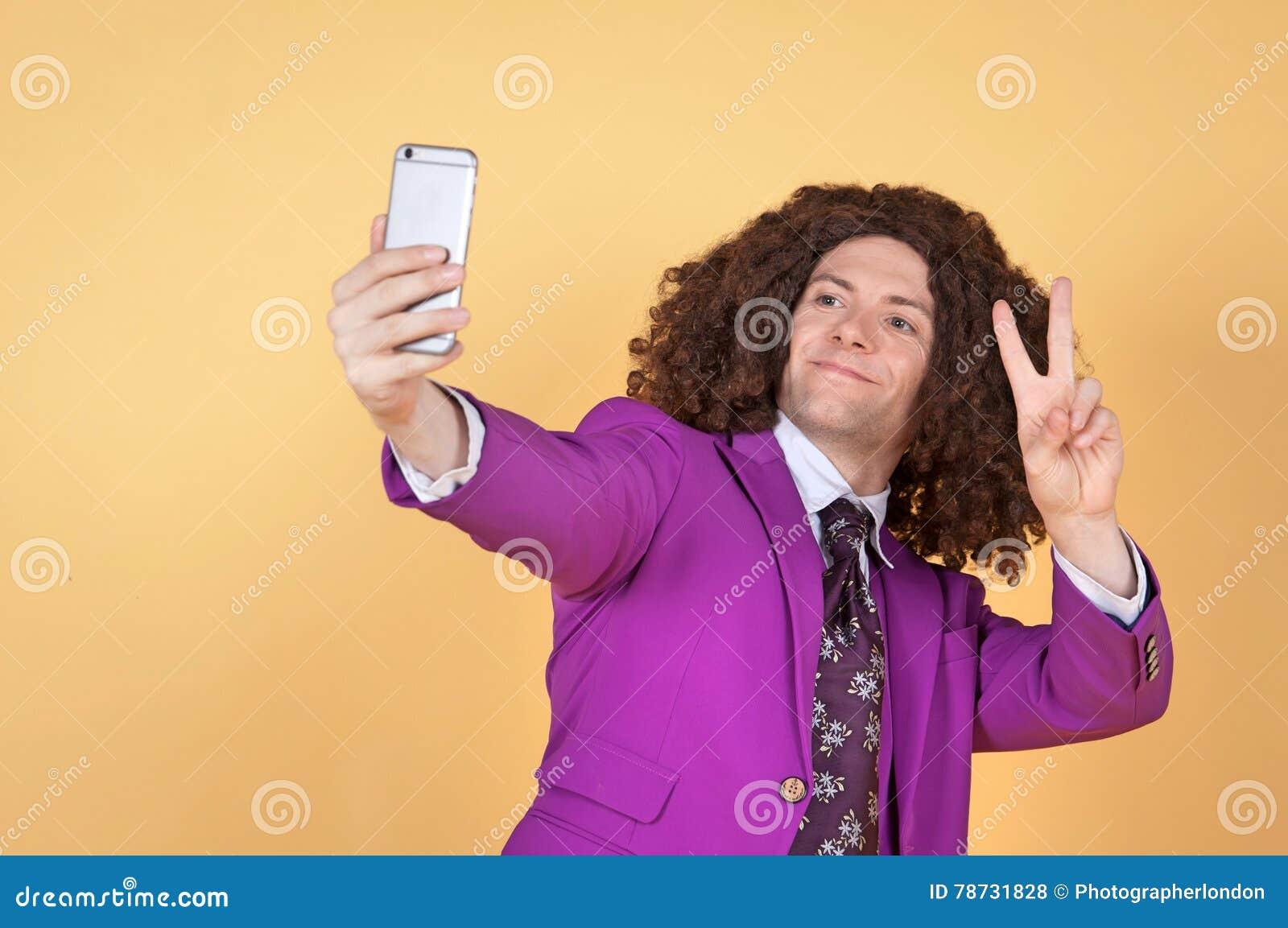 Den Caucasian mannen med afro bärande lilor passar ta en selfie