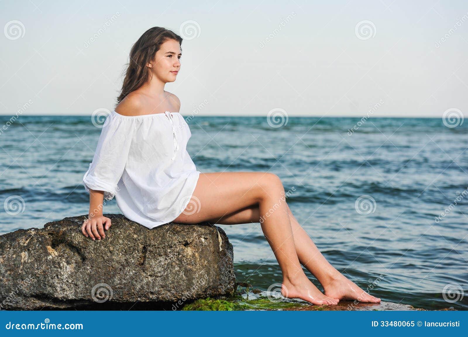 Den Caucasian tonåriga flickan i bikinin och vitskjortan som är slö på lava, vaggar vid havet