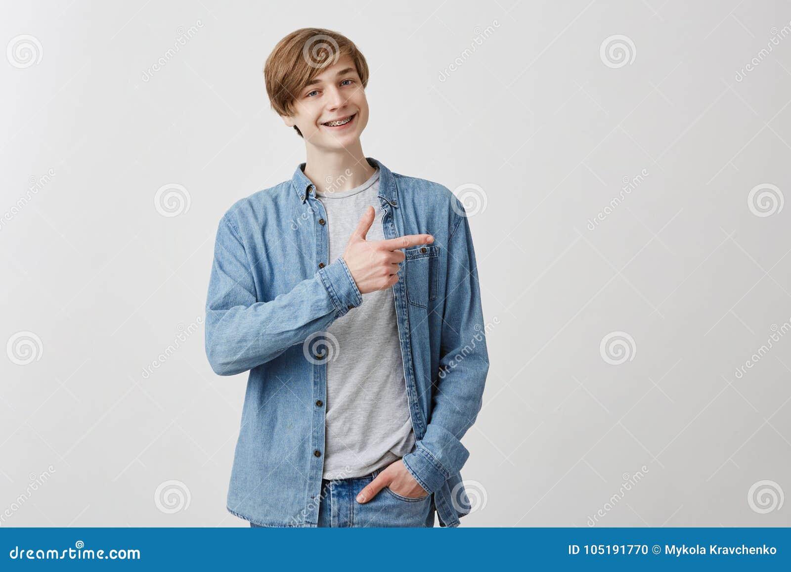 Den Caucasian unga mannen grinar på kameran, indikerar på kopieringsutrymme, annonserar något Lyckliga manpunkter med främre fiin