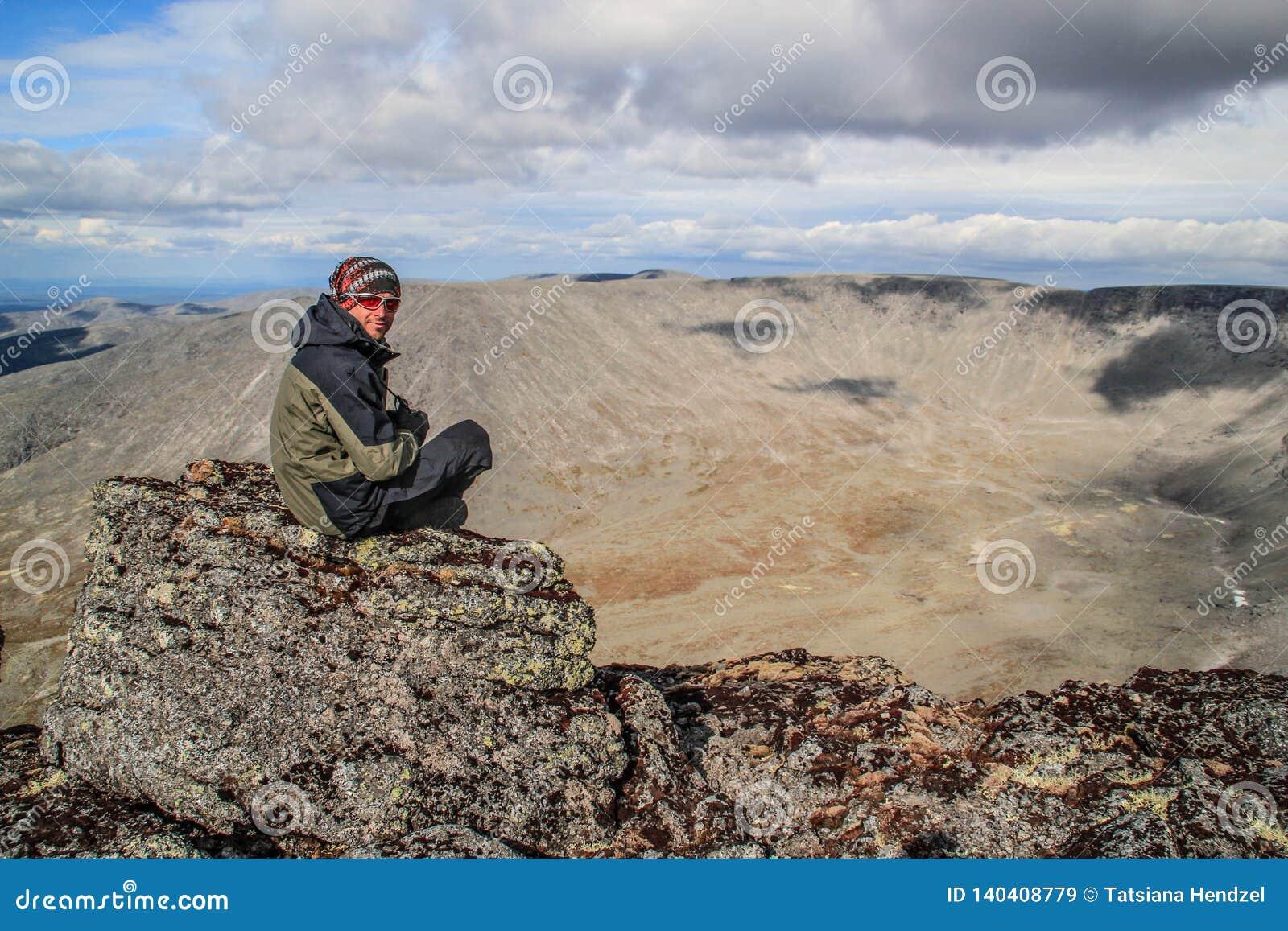 Den Caucasian vita manliga turisten i sportswear, fantast och exponeringsglas sitter på vaggar