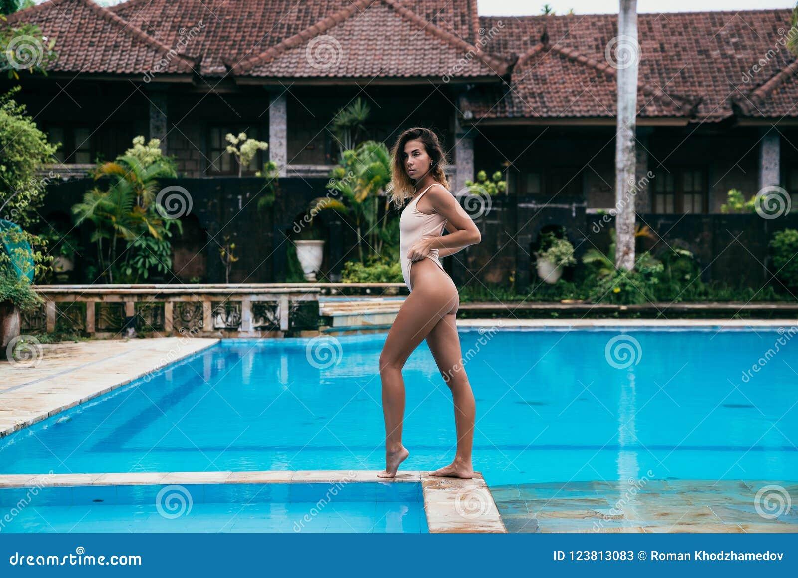 Den charmiga flickan med lockiga hår i en baddräkt med härliga sportar figurerar att posera nära simbassängen och att tycka om