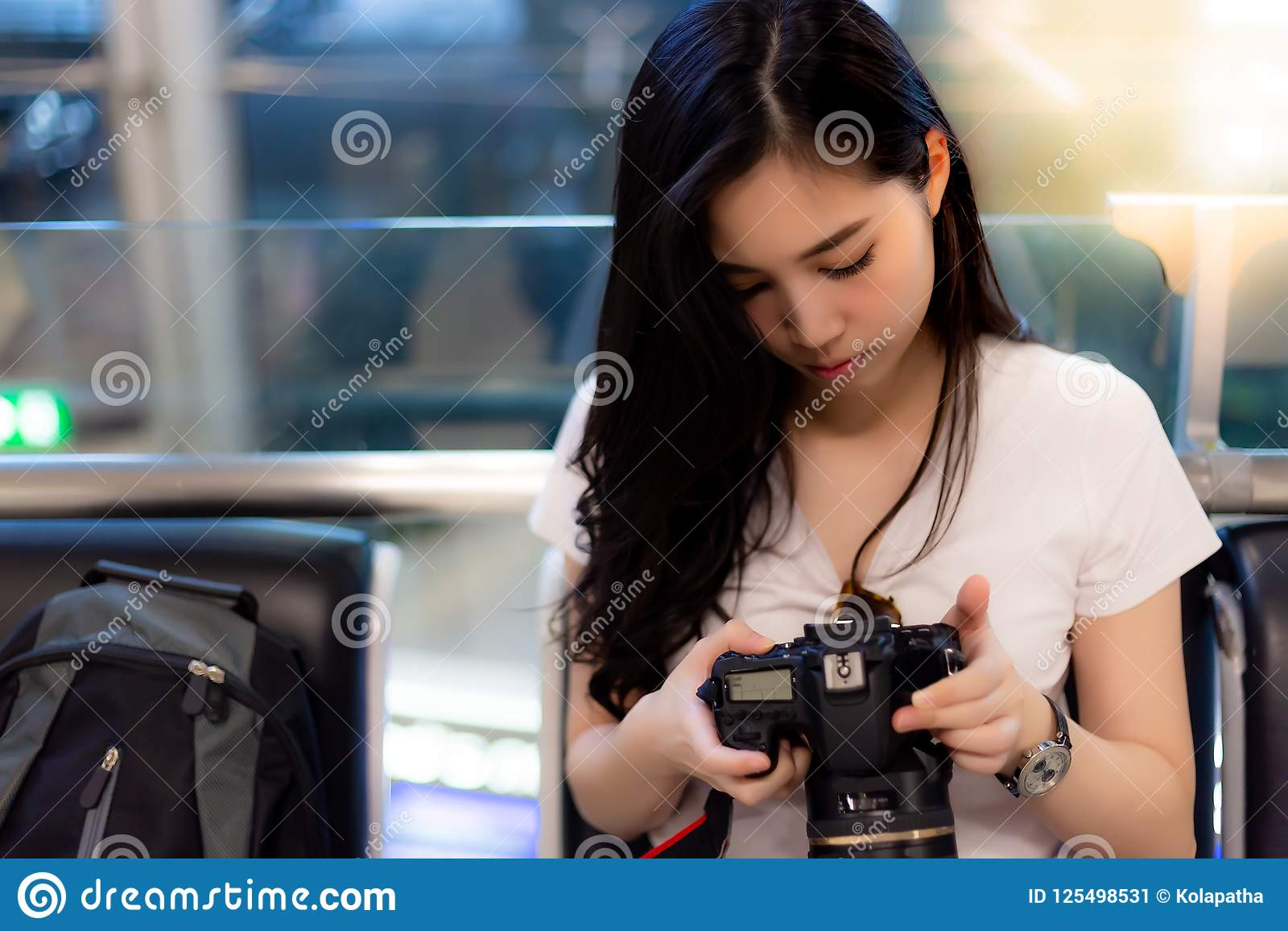 Den charmiga härliga kvinnan kontrollerar hennes kamera och foto för traveli