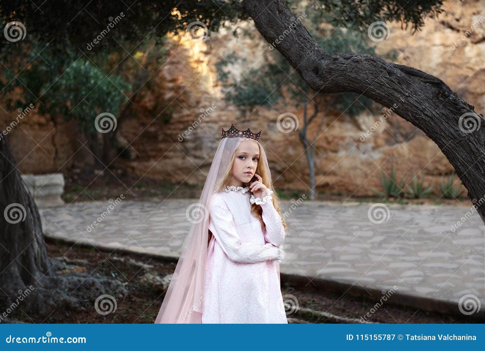 Den charmiga vita häxaforetelleren står i en mystisk magisk skog i en bröllopsklänning med en skyla och en krona