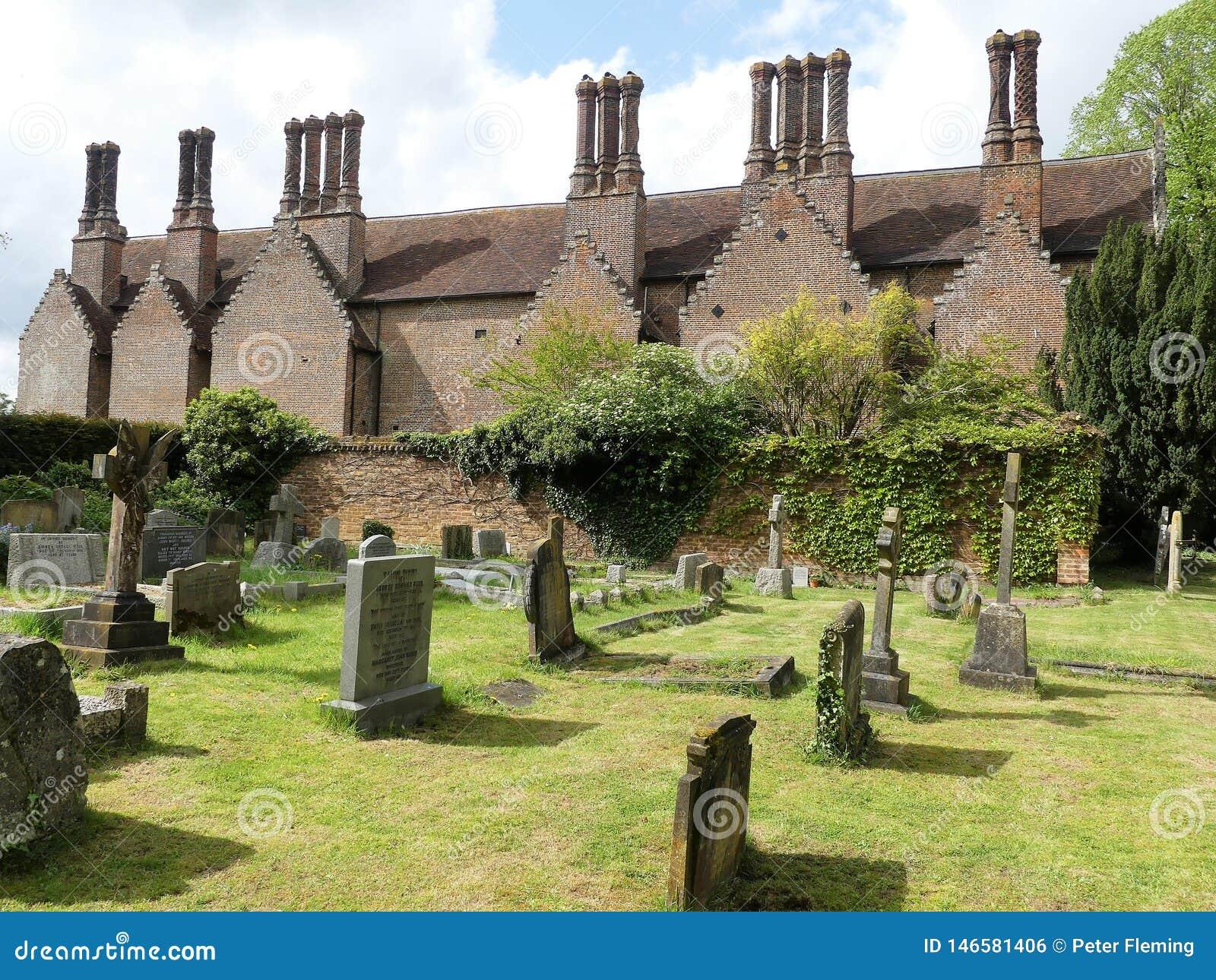 Den Chenies mangårdsbyggnaden, en Tudor Grade listade jag byggnad, med den kyrkliga kyrkogården i förgrund