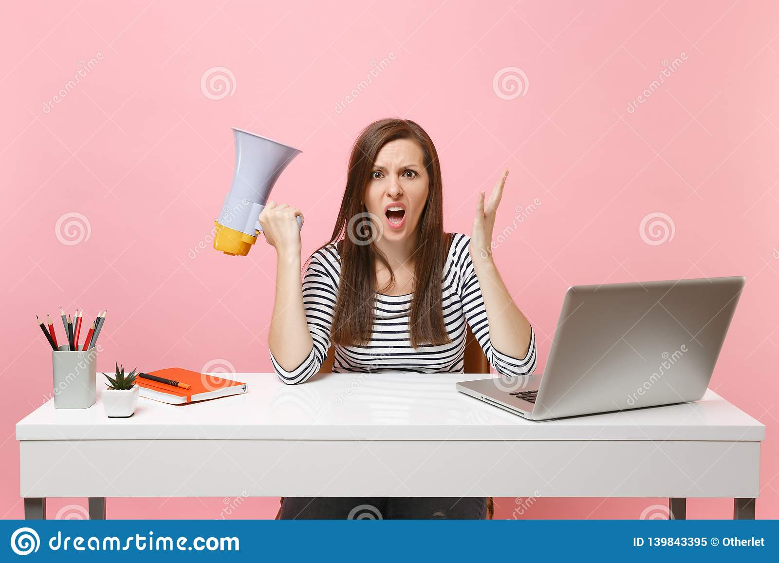 Den chockade ilskna kvinnan som skriker fördelande händer som rymmer megafonen, sitter och arbetar på det vita skrivbordet på kon