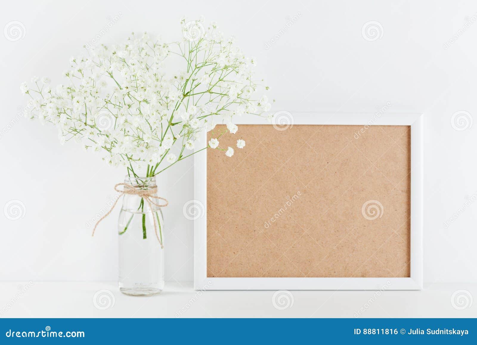 Den dekorerade modellen av bildramen blommar i vas på det vita funktionsdugliga skrivbordet med rent utrymme för text och planläg