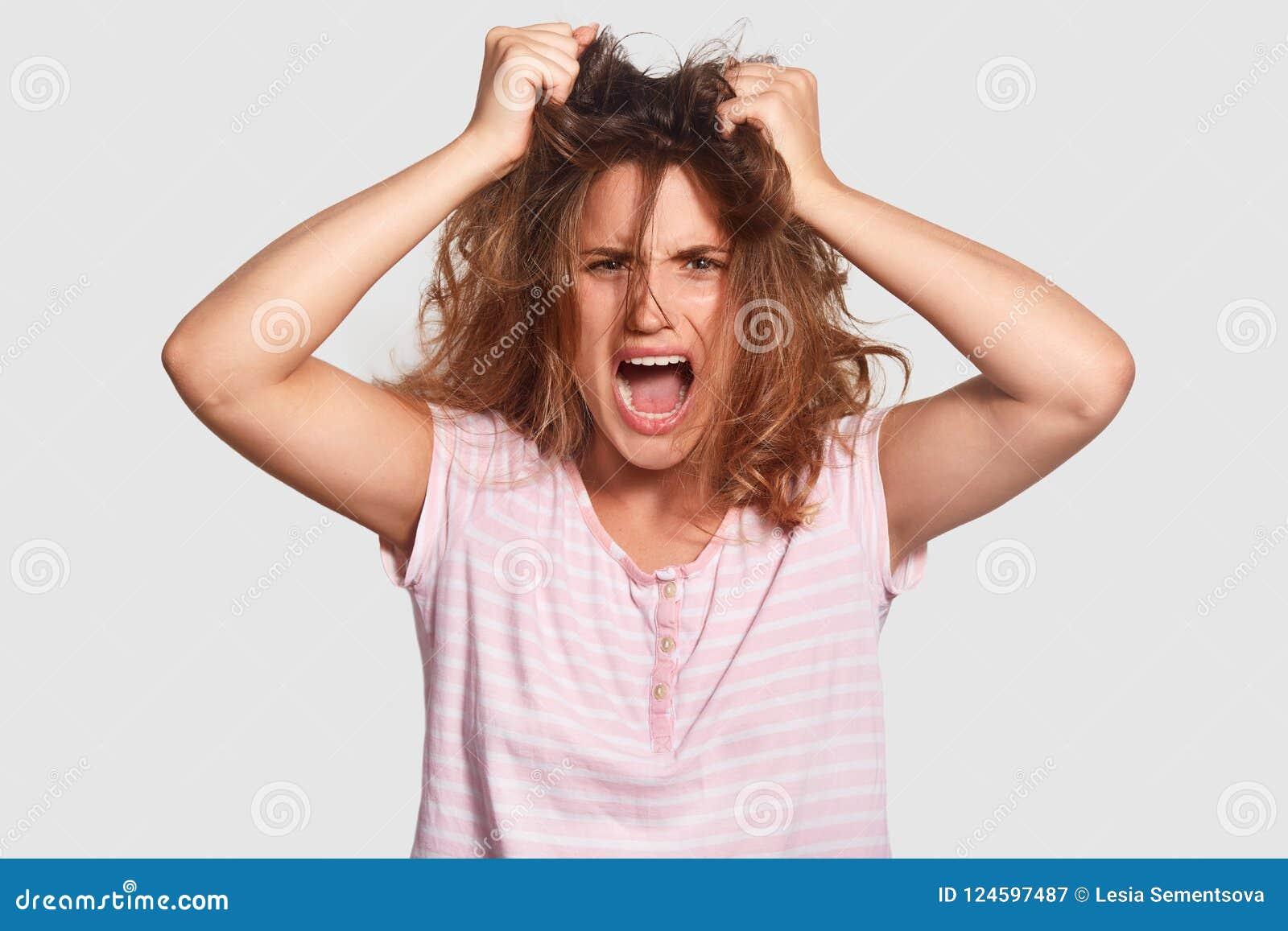 Den deprimerade irriterade unga kvinnlign har röra på hår, öppnar munnen brett, ropar angrily, önskar inte får upp, matat upp av