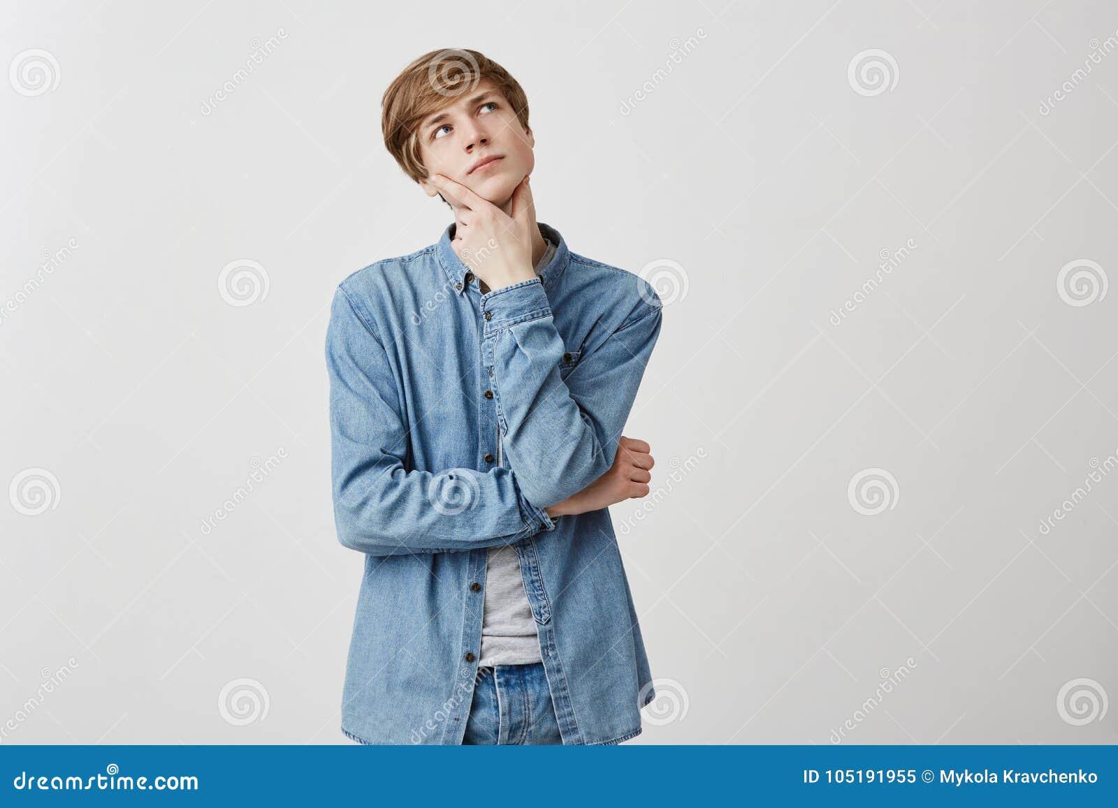 Den eftertänksamma unga mannen med ganska hår och blåa ögon, har allvarligt ansiktsuttryck, ser upp, uppehällefingrar under hakan