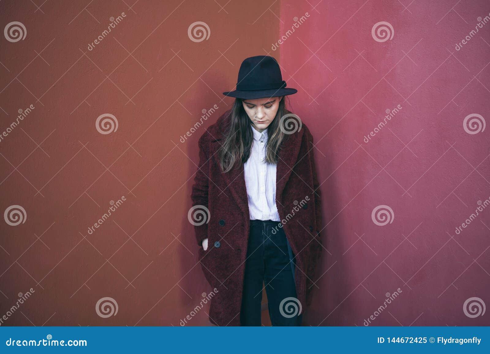 Den eftertänksamma unga tonåriga flickan står mot den röda väggen Ledset tvivlar Melankoliskt lynne som bara är med dig