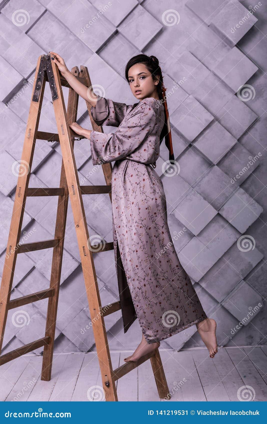 Den eleganta charmiga kvinnlign som gör artigt, poserar under studioskytte