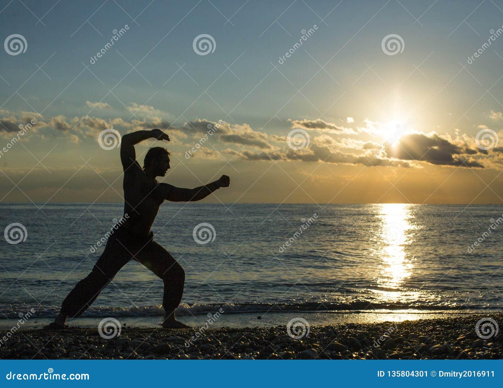 Den enkla mannen gör kampsporter på stranden under solnedgångtid Wushu