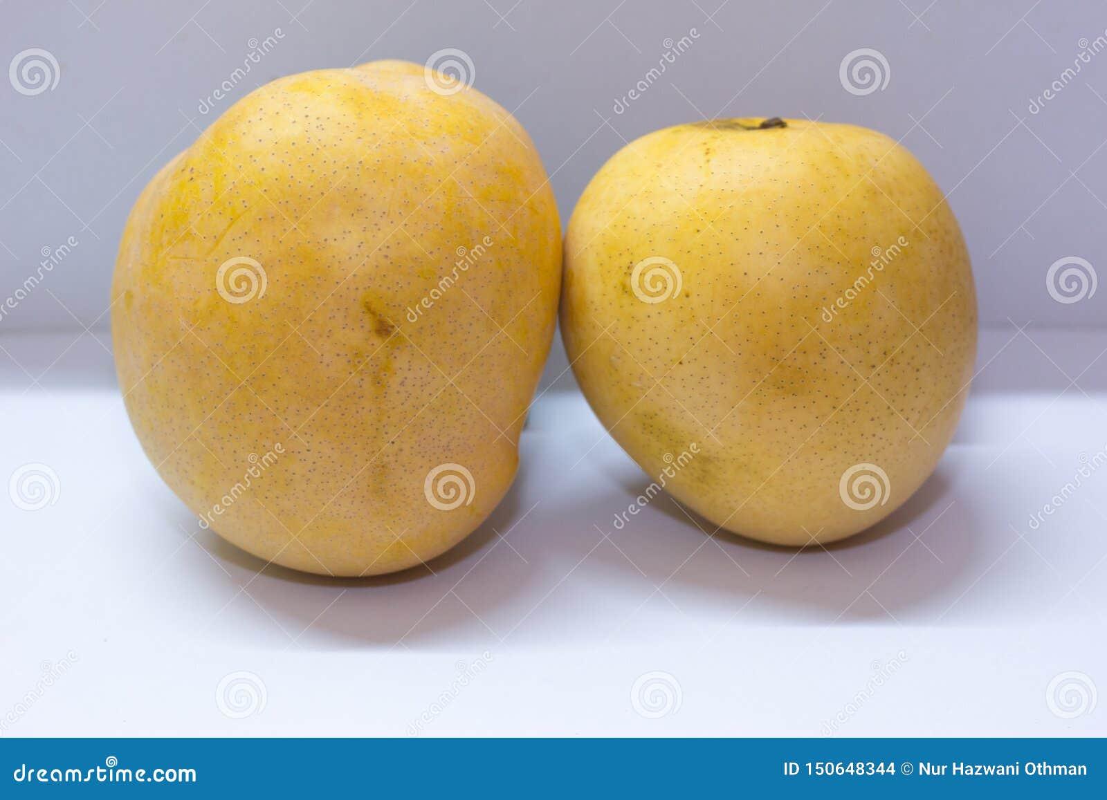 Den enorma mango två på vit bakgrund med en bra arom