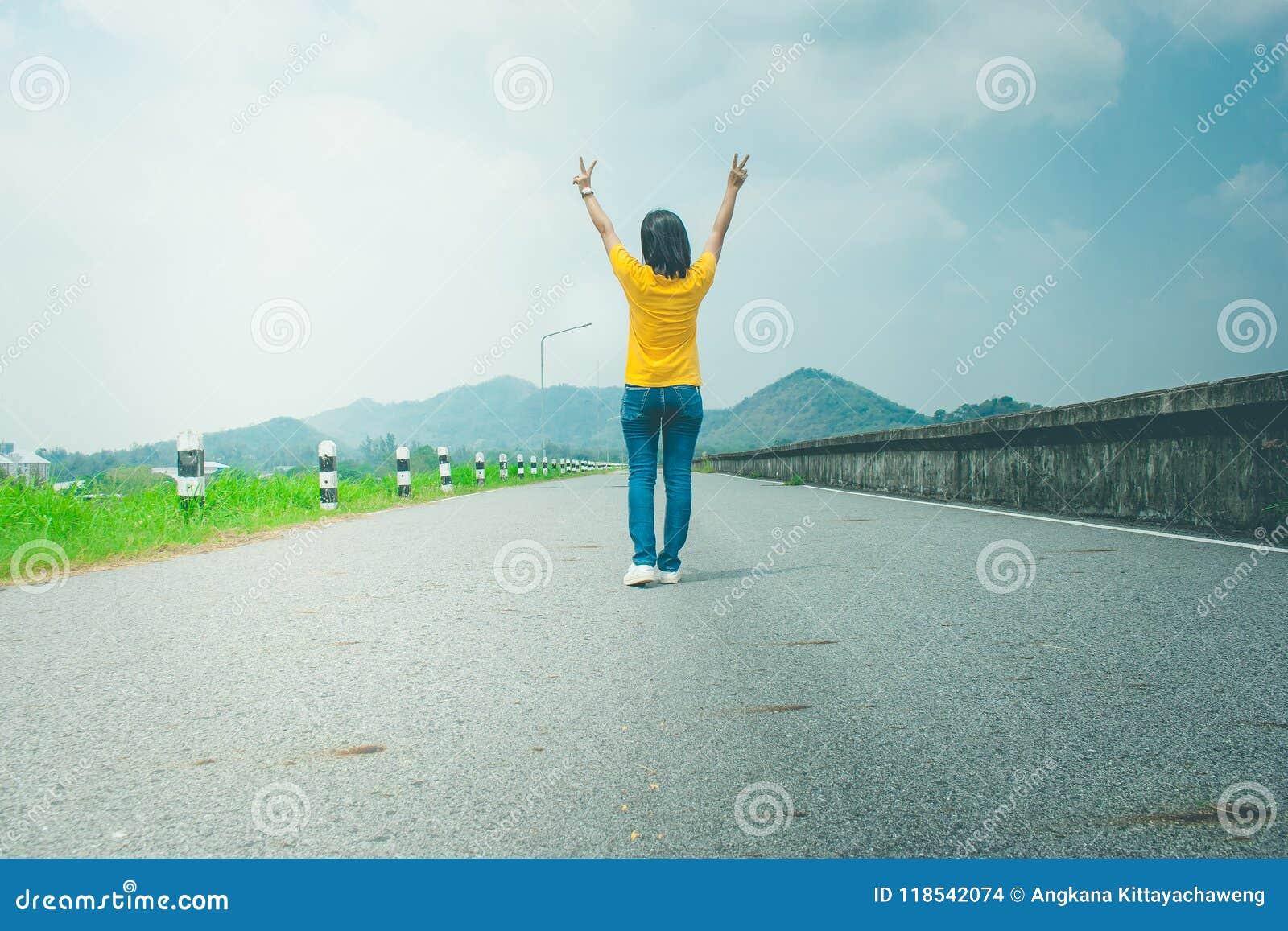 Den ensamma den kvinnahandelsresanden eller fotvandraren som promenerar bygdvägen längs sida med behållaren, lyfter hon händer up