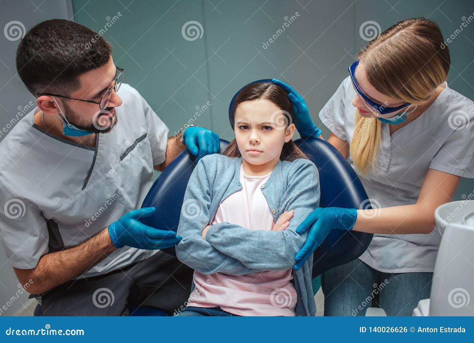 Den envisa flickan sitter i ddental cair i rum Tandläkare ser oroat hennes De trycker på och talar till henne På green