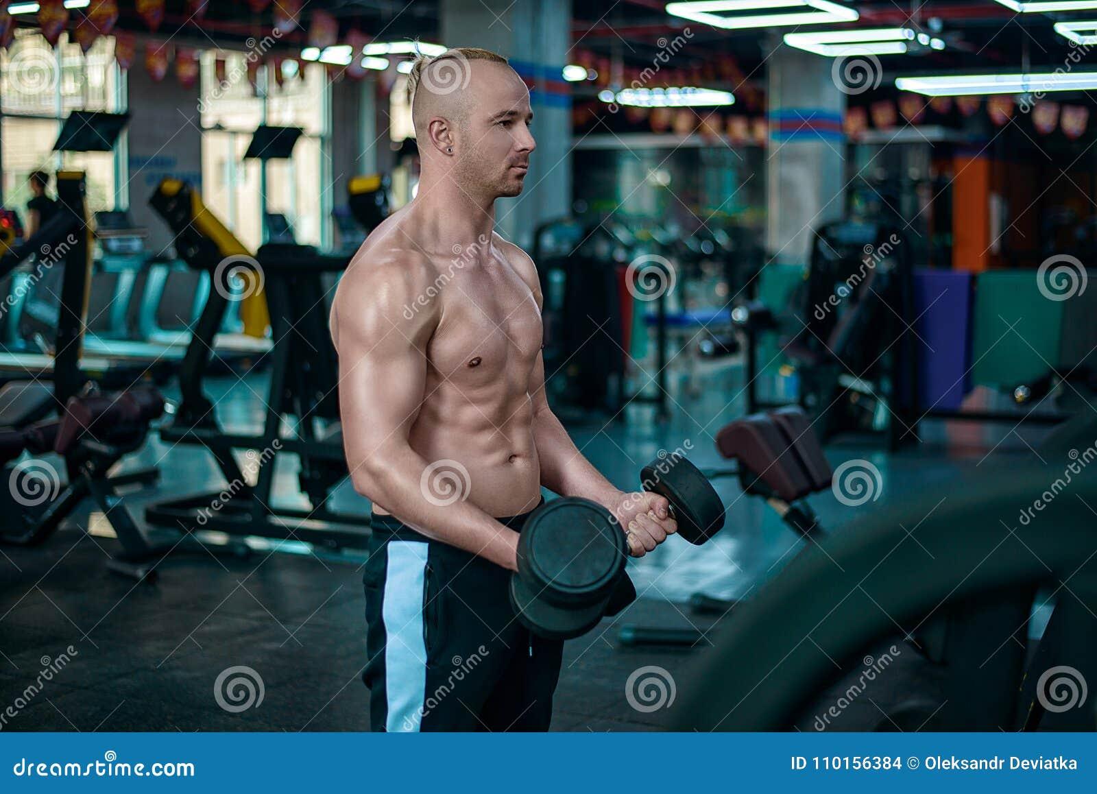 Den europeiska mannen gör övningen för biceps med hantlarna