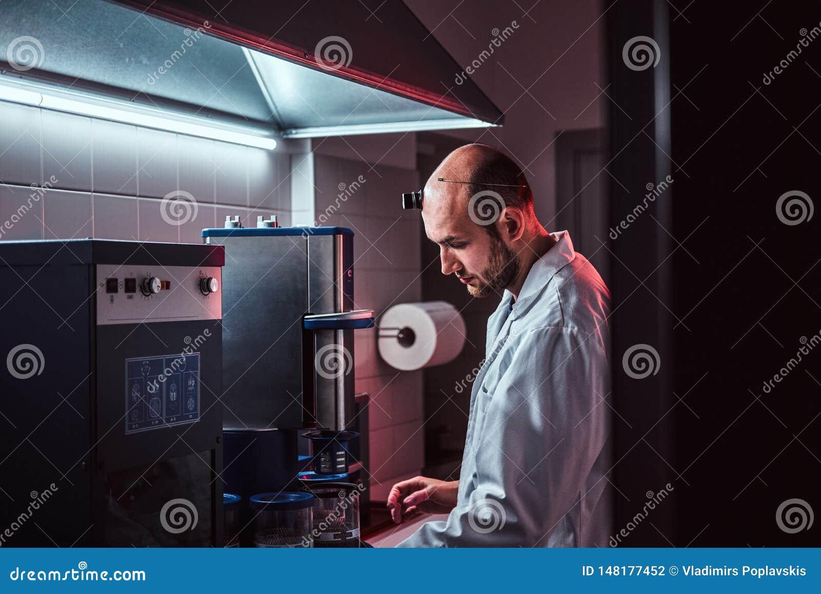Den Expirienced urmakaren arbetar med autoclaven p? hans egen studio