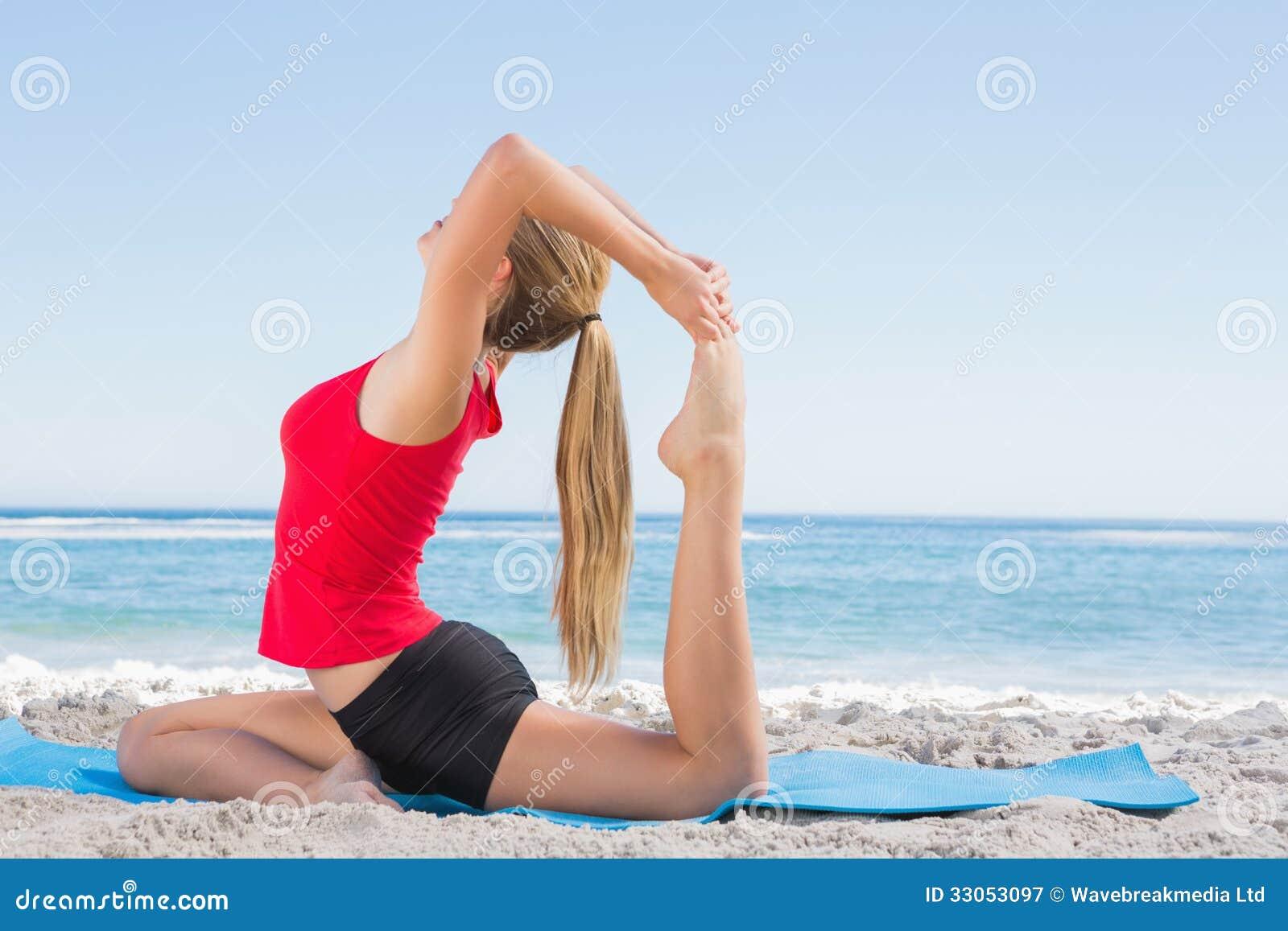 Den färdiga blondinen som sträcker benet i yoga, poserar