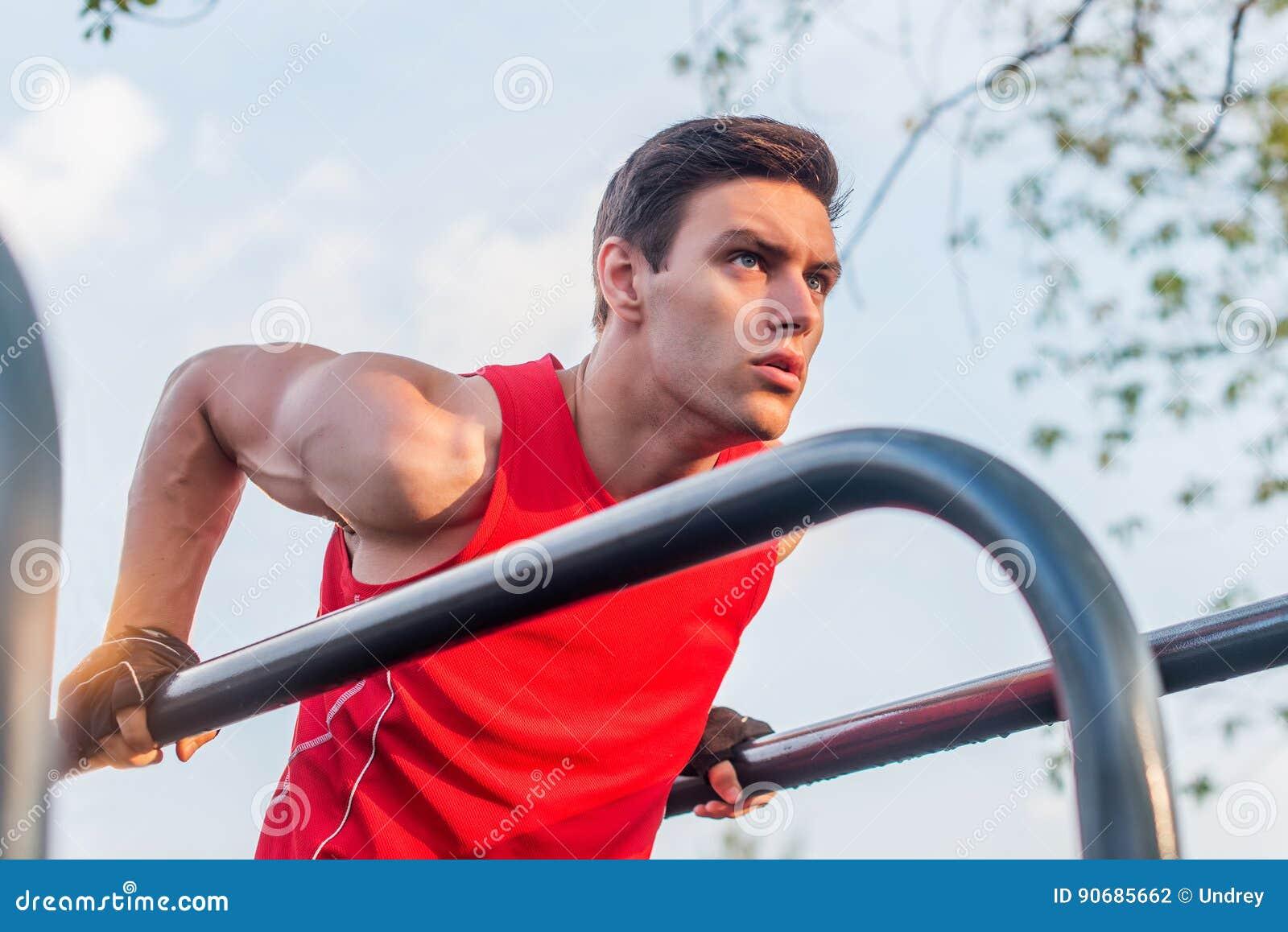 Den färdiga mannen som gör triceps, doppar på barr på parkerar att öva utomhus