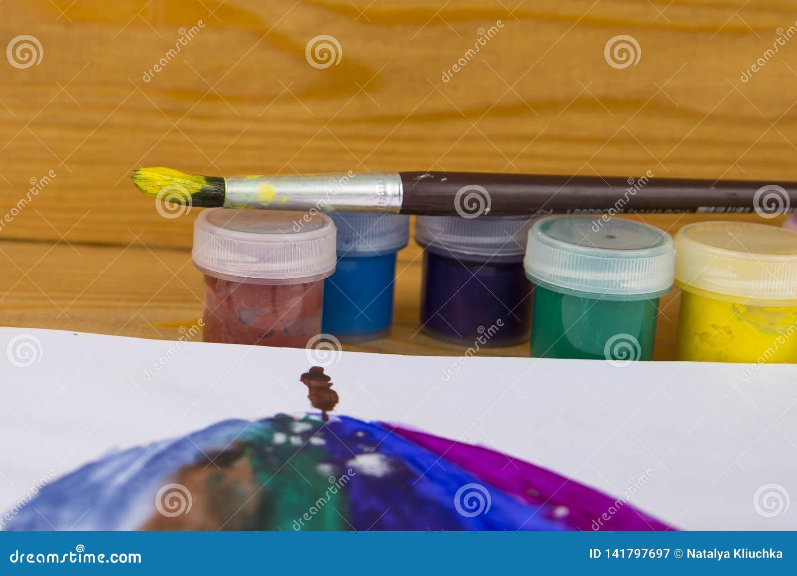 Den färgade gouachen på burk på träbakgrund, målarfärg för teckning Dagis och skola Multi-colored målarfärg Kreativitet för barn`