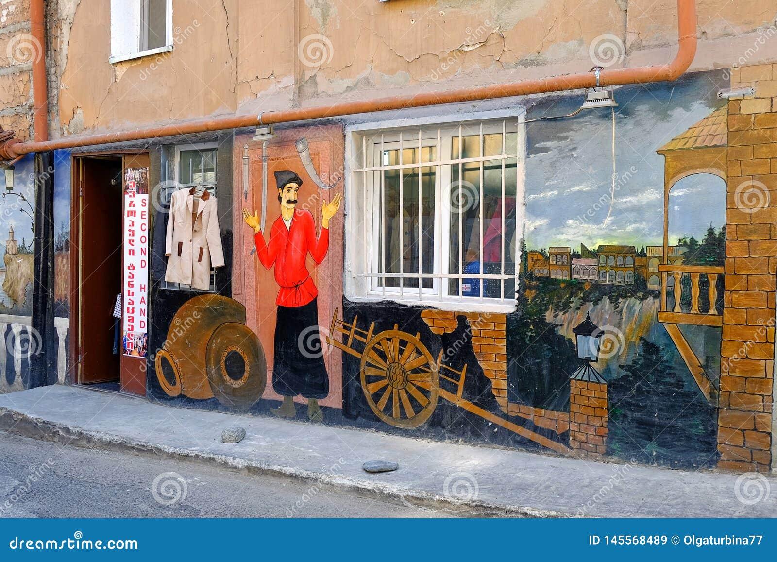 Den färgrika artistically målade väggen av det gamla huset i gammal del av Tbilisi visade plats av lokalt traditionellt dagligt l