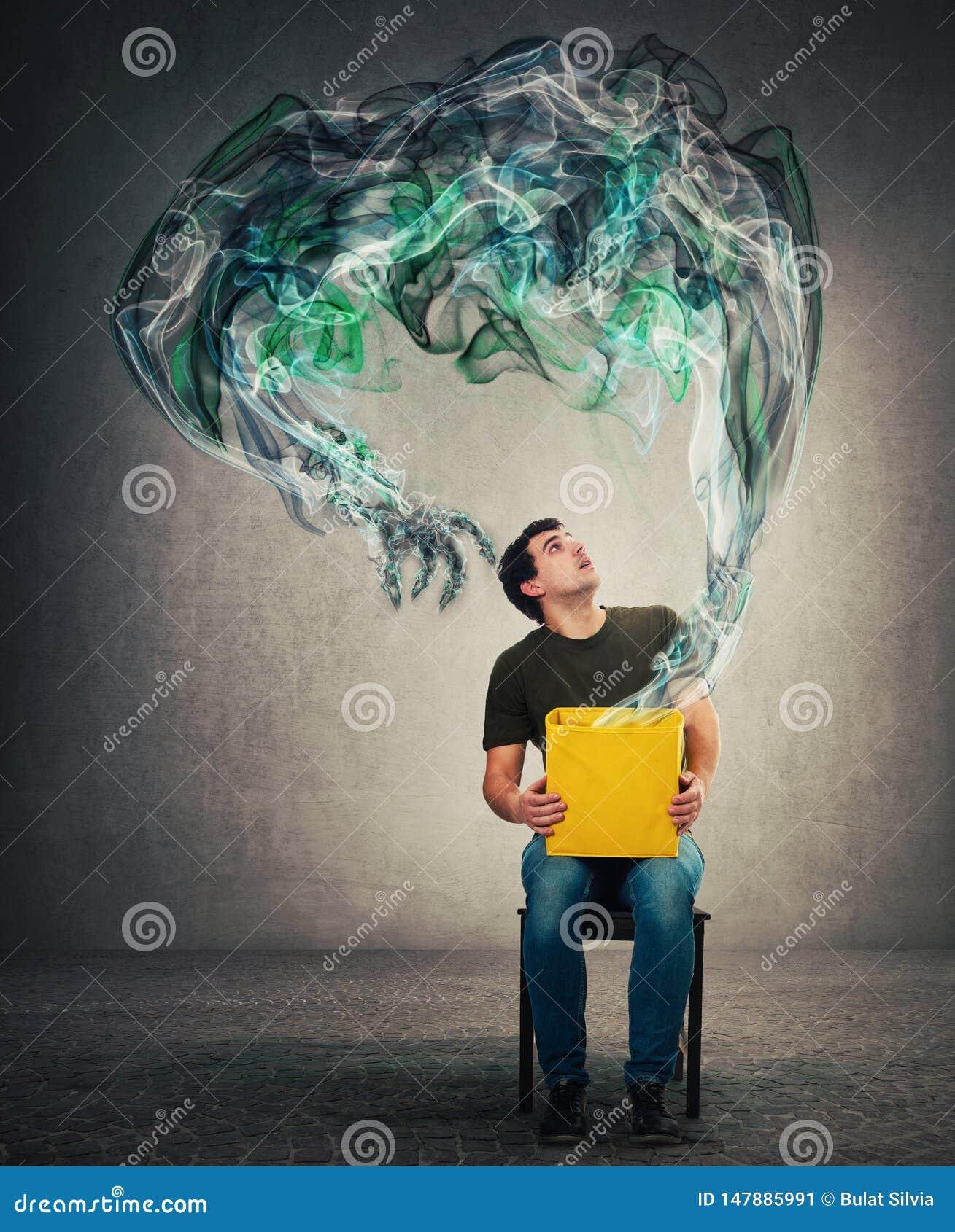 Den förskräckta mannen som placeras på en stol som rymmer gåtaasken på knä som ser upp med chockat uttryck som en mörk rök för my