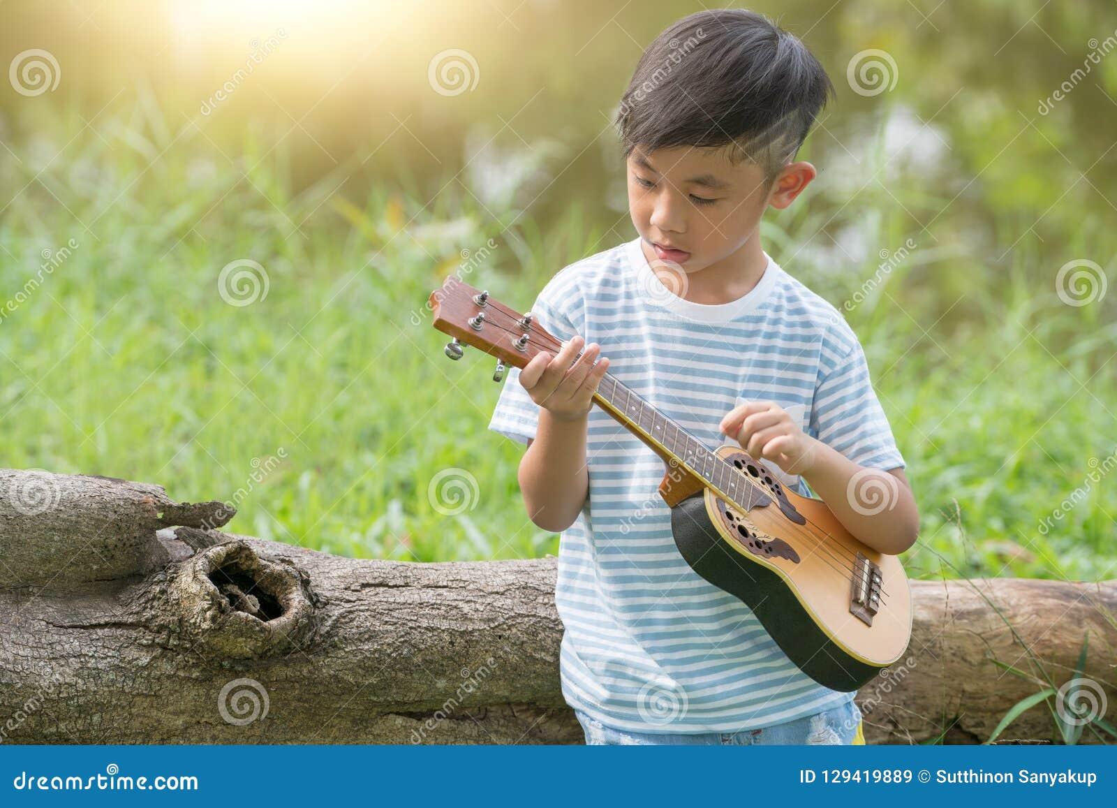 Den förtjusande pojken med gitarren som sitter på gräset på solnedgång, det musikaliska begreppet med pysen som spelar ukulelet p