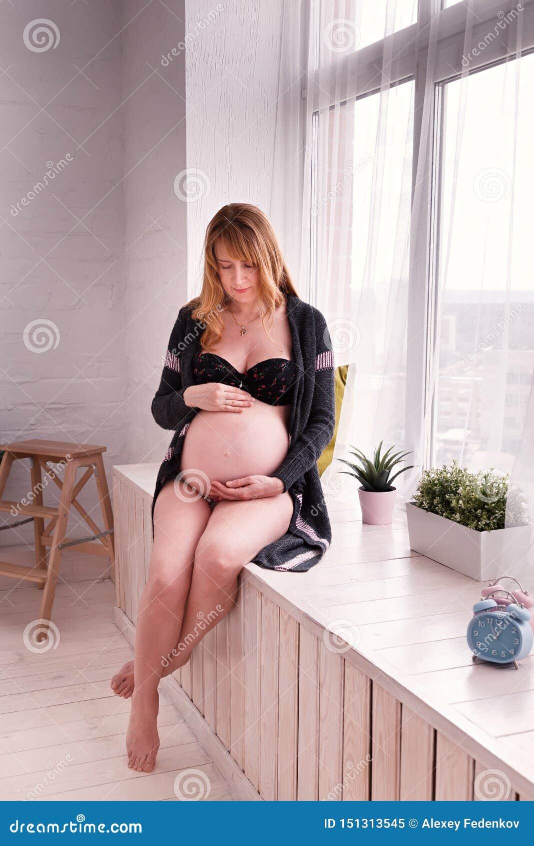 Den förväntansfulla modern som sitter vid fönstret och ser försiktigt, buken som är hennes framtida barn är