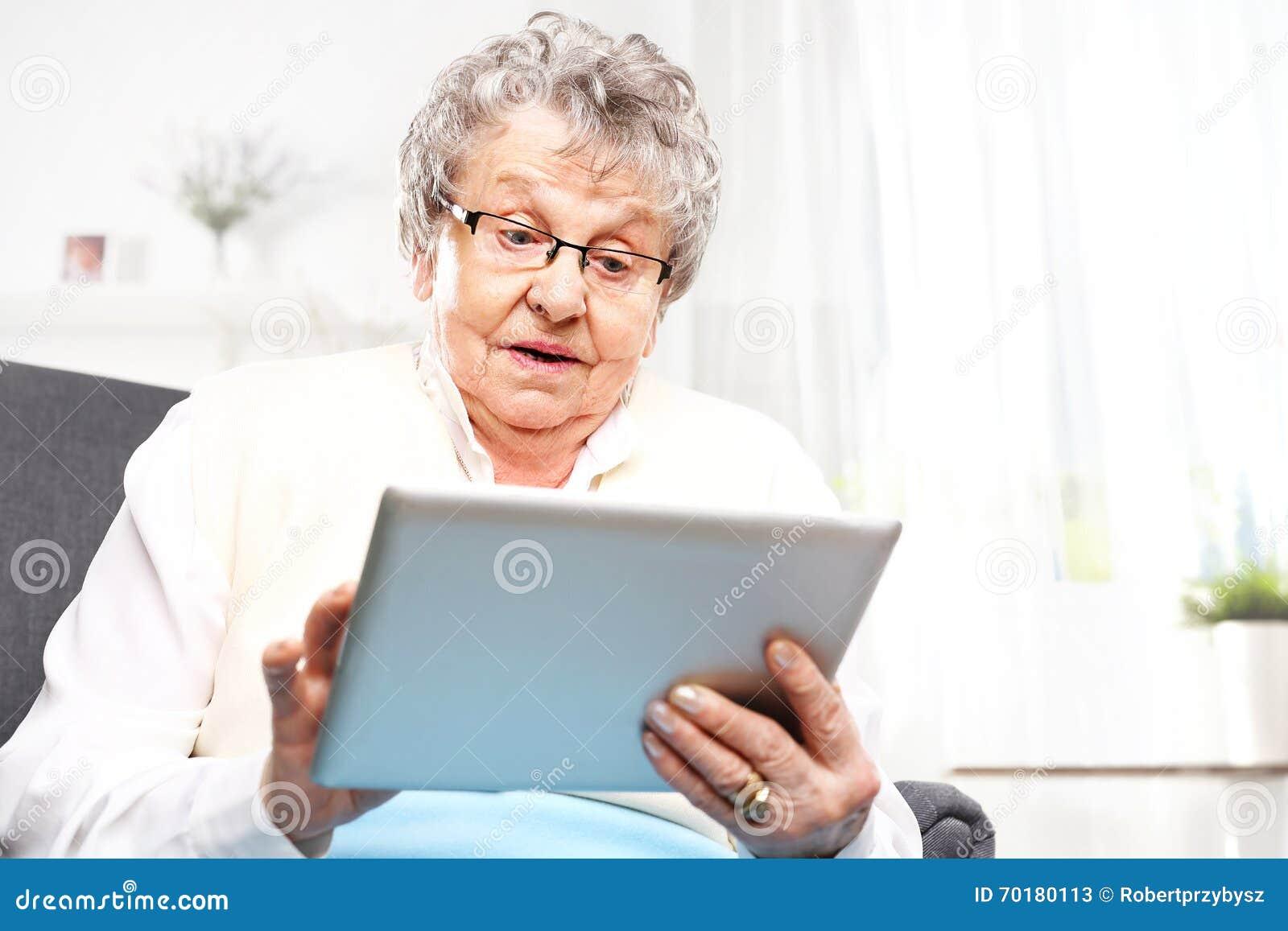 Den förvånade äldre kvinnan ser i minnestavlaskärmen