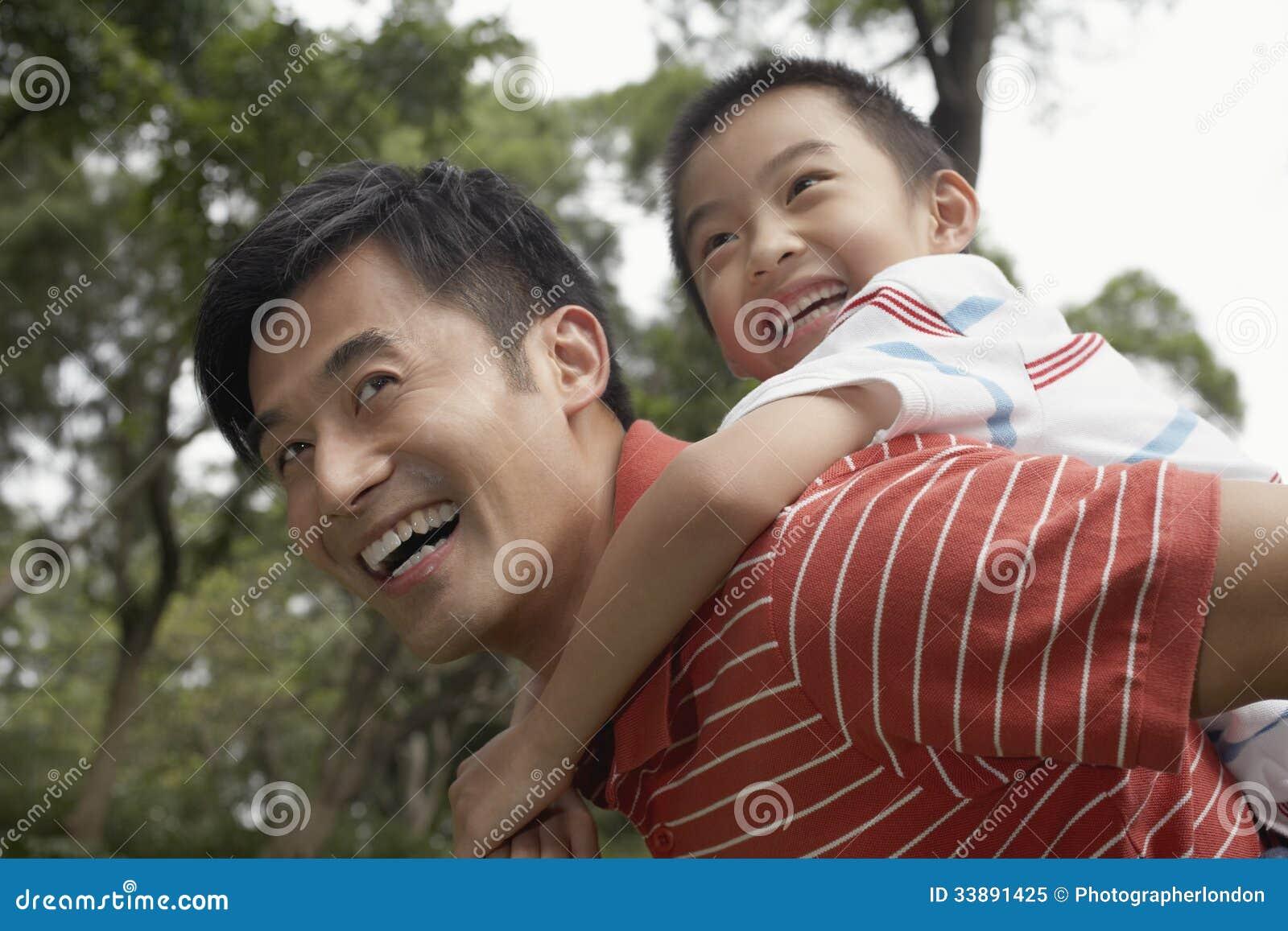 Den faderAnd Son Enjoying på ryggen ritten parkerar in