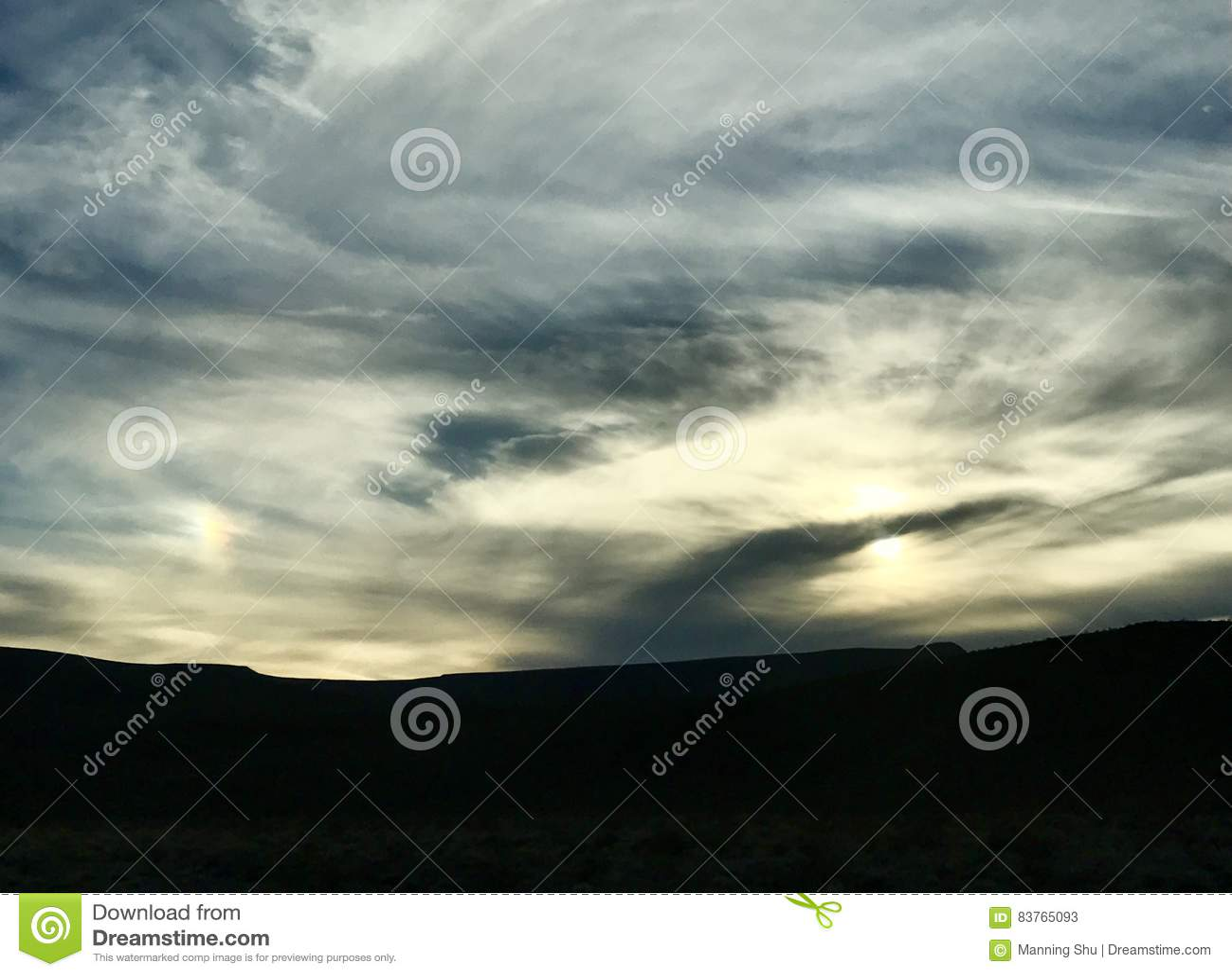Den fjäderlika soluppgångsolnedgången fördunklar över blått- och gulinghimmel