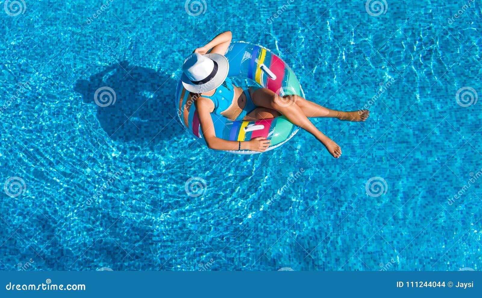 Den flyg- bästa sikten av den härliga flickan i simbassäng från över, kopplar av bad på den uppblåsbara cirkelmunken och har gyck