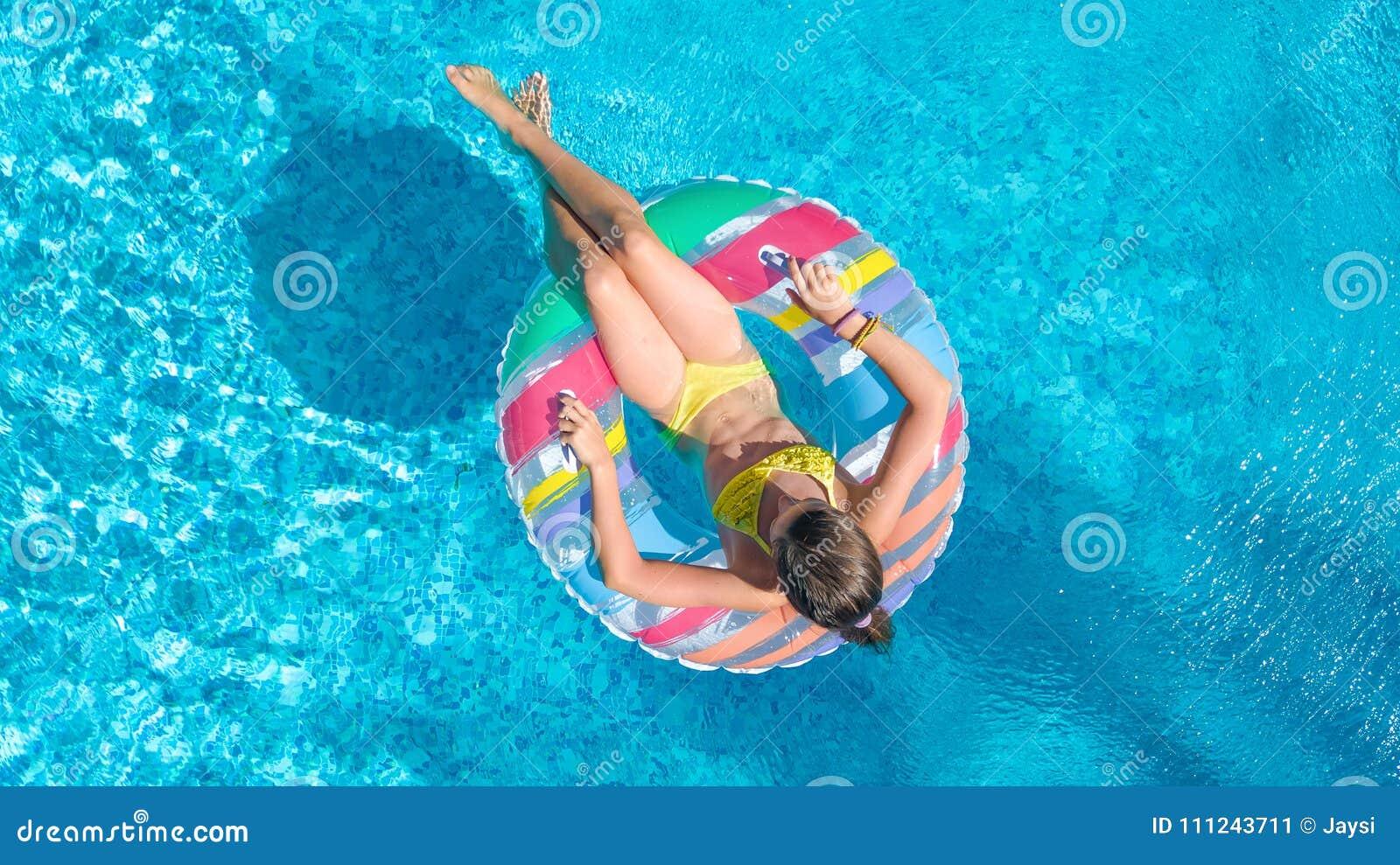 Den flyg- bästa sikten av lilla flickan i simbassäng från över, ungebad på den uppblåsbara cirkelmunken, barn har gyckel i vatten