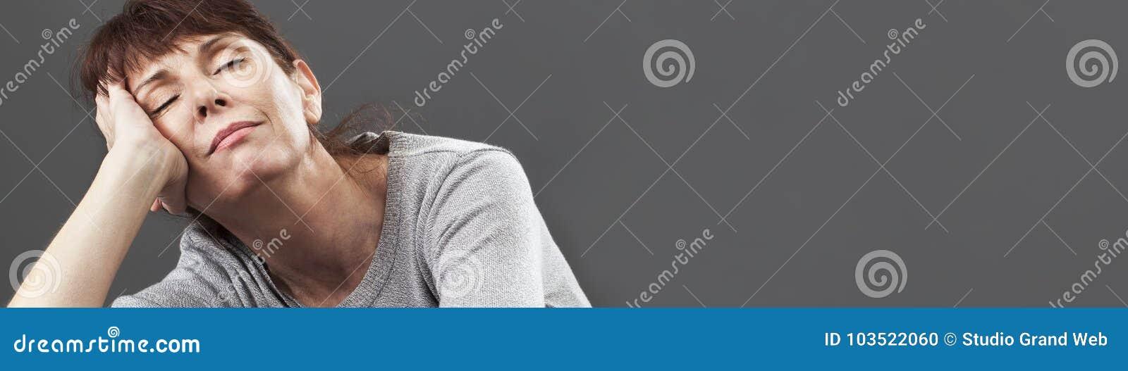 Den fridfulla 50-talkvinnan som tycker om, ta sig en tupplur ligga på kuddar, grått baner