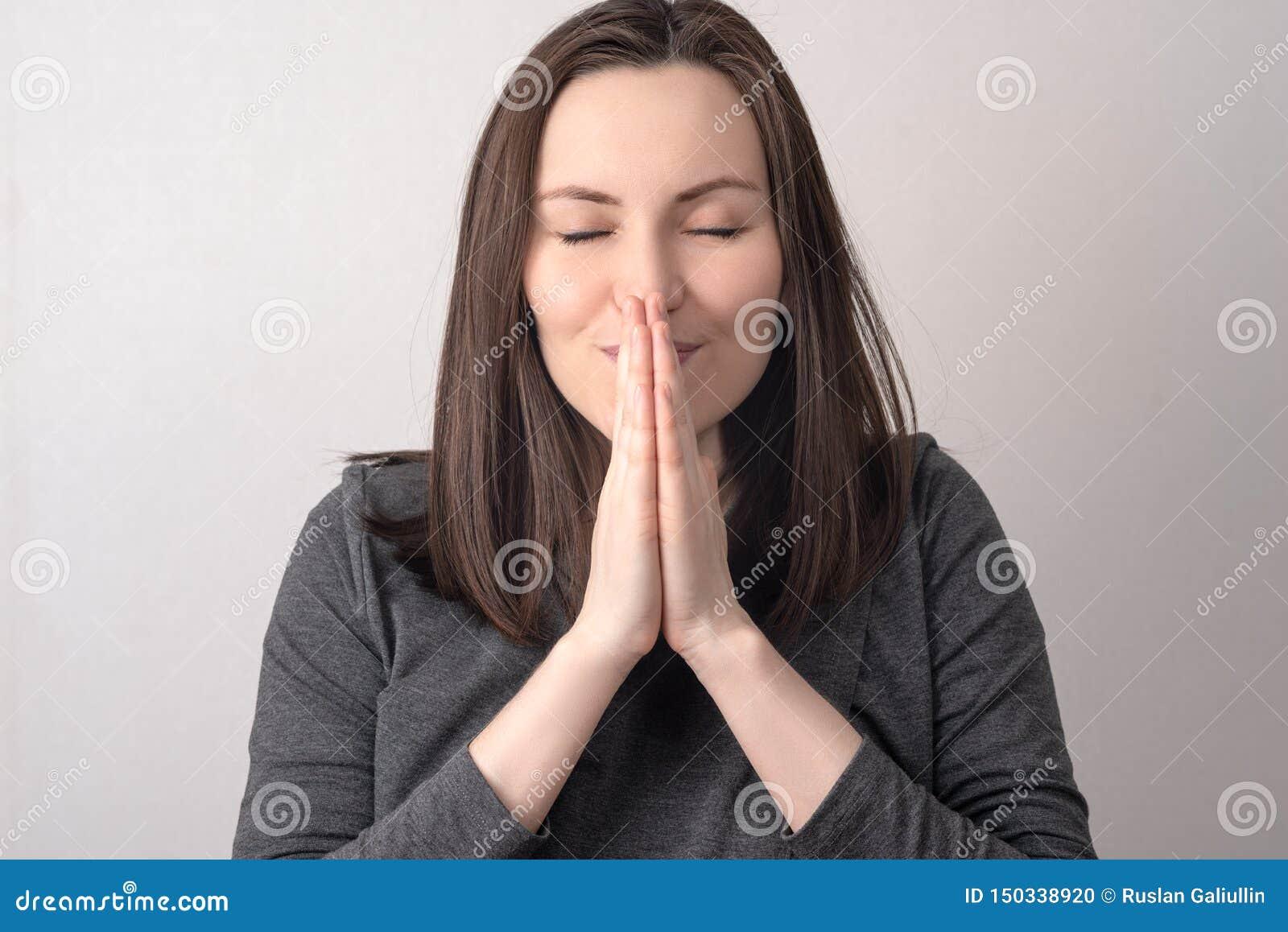 Den Frontal närbildståenden av en kvinna vek hennes händer framme av hennes framsida, bön, gör en önska