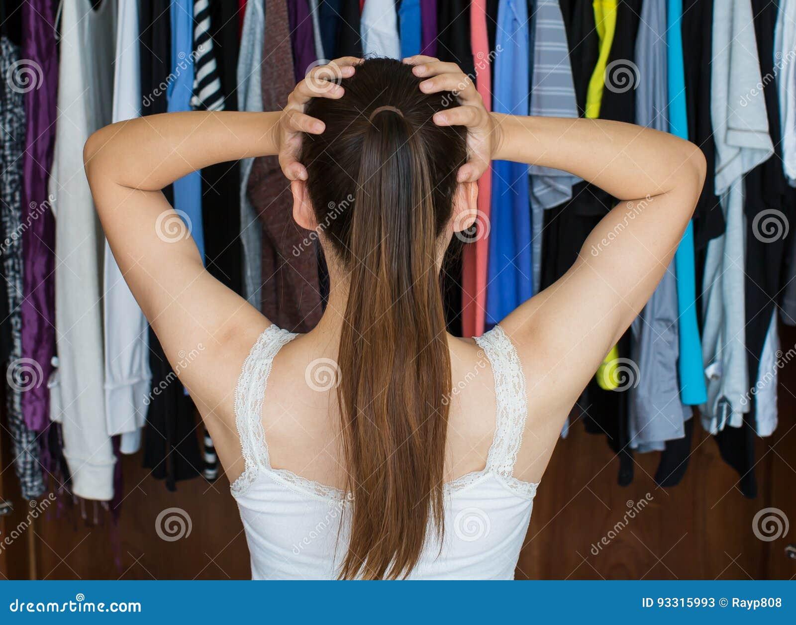 Den frustrerade unga kvinnan kan inte avgöra vad för att bära från hennes slut