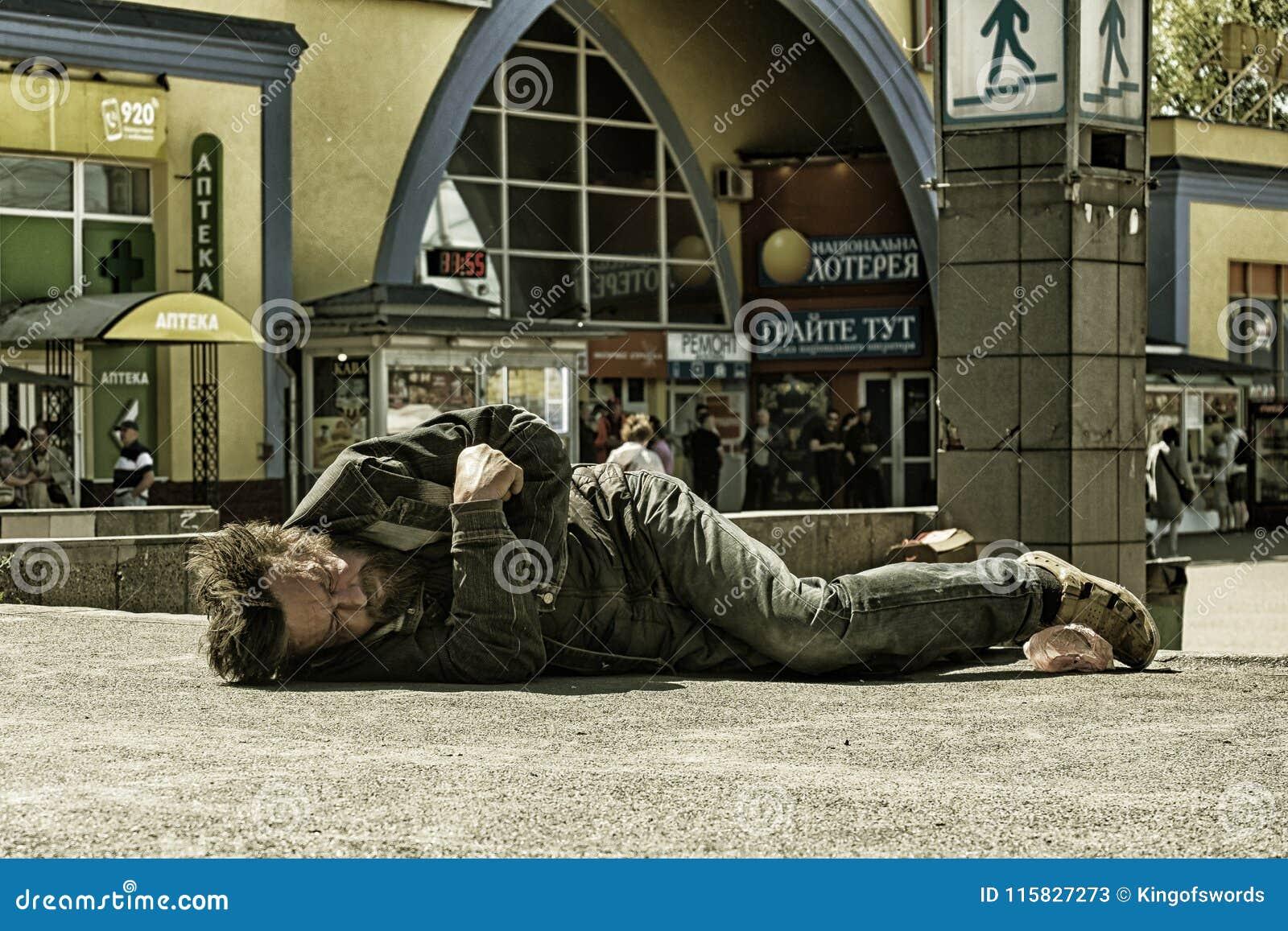 Den fulla hemlösa mannen sover på betong i brett dagsljus