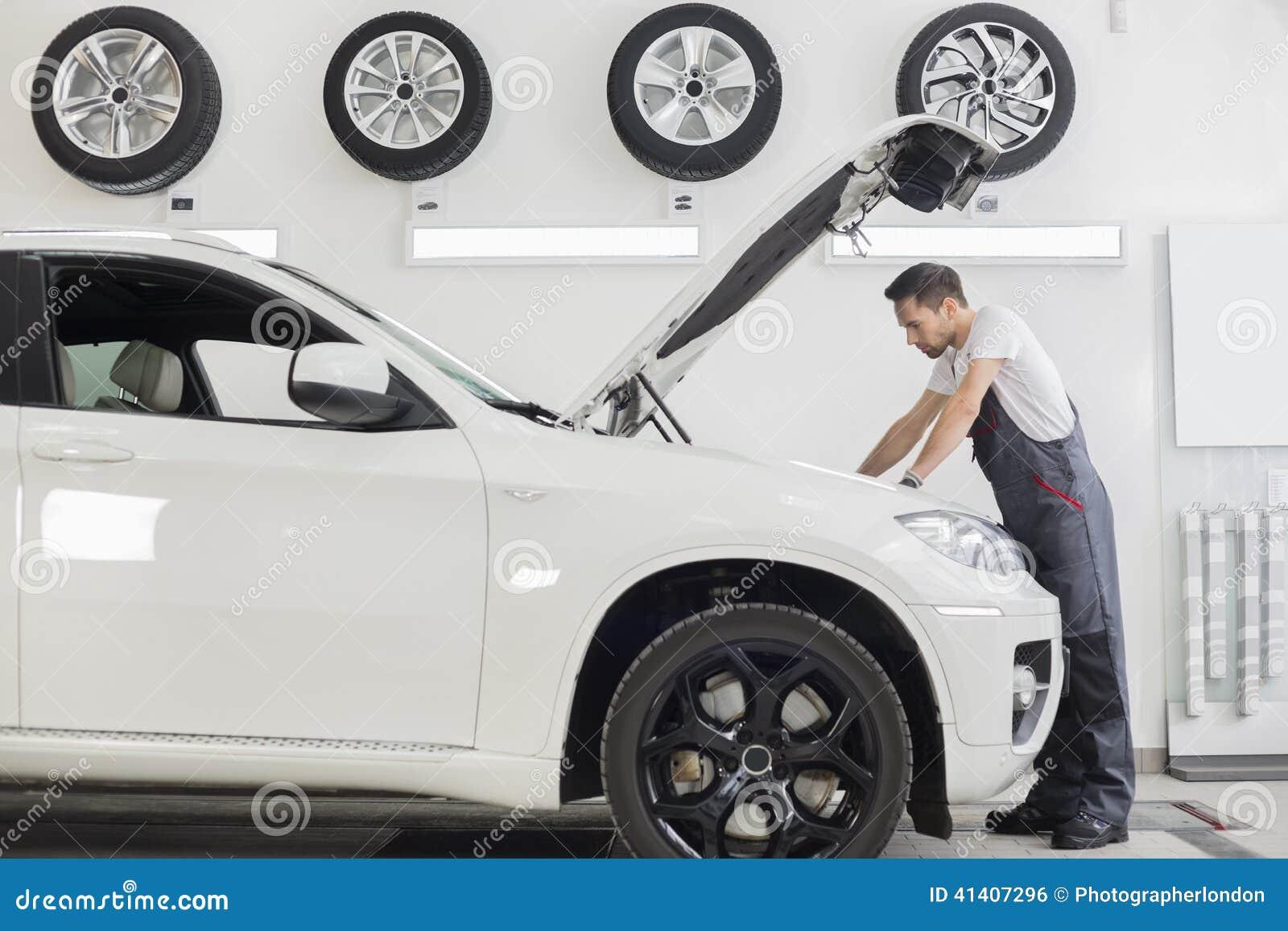 Den fulla längdsidosikten av den undersökande bilmotorn för den manliga mekanikern i reparation shoppar