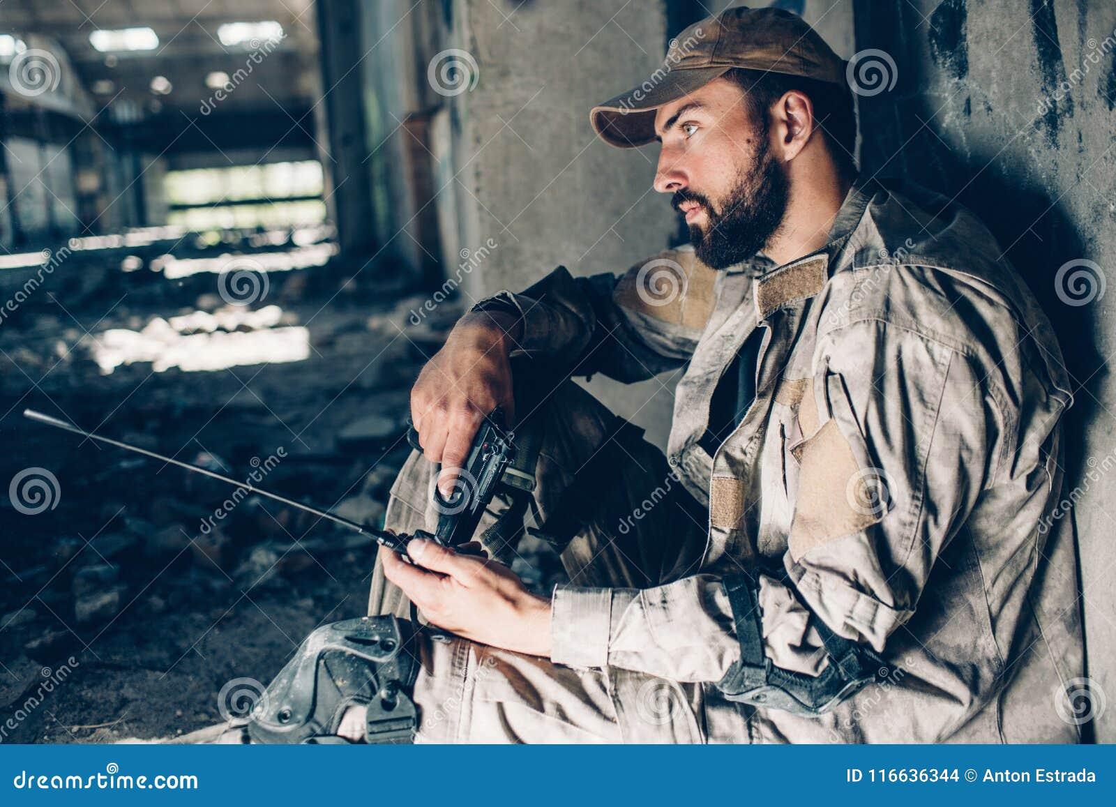Den fundersamma grabben i likformig sitter på jordningen och benägenheten till väggen Han ser rättfram Krigaren är trött