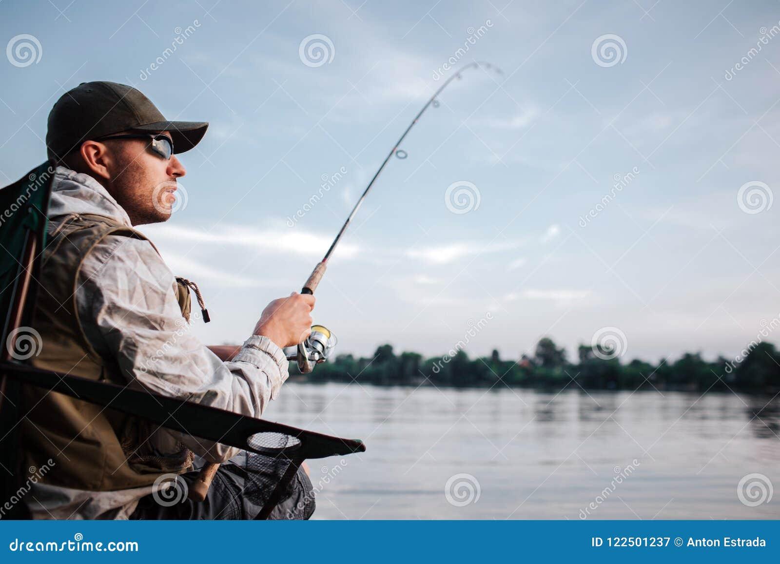 Den fundersamma grabben sitter på kanten av vatten och ser till rätten Han rymmer den klipska stången i händer Det är aftonen och
