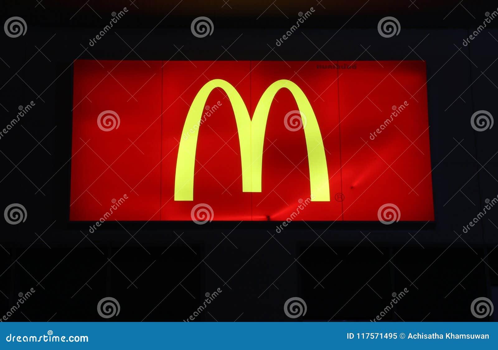 Den fyrkantiga ljusa asken av logoen för McDonald ` s på natten framme av Tesco Lotus Discount Store