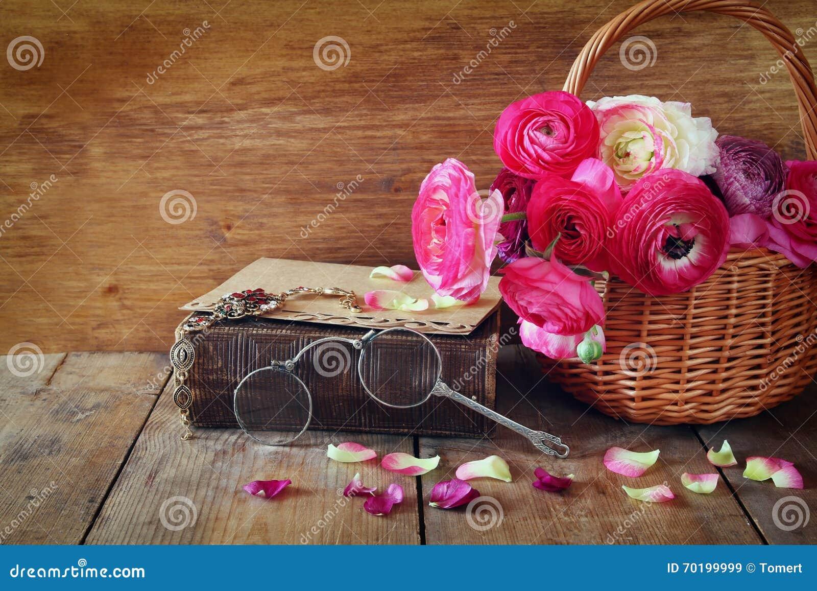 Den gamla boken och exponeringsglas bredvid härligt fält blommar på trät
