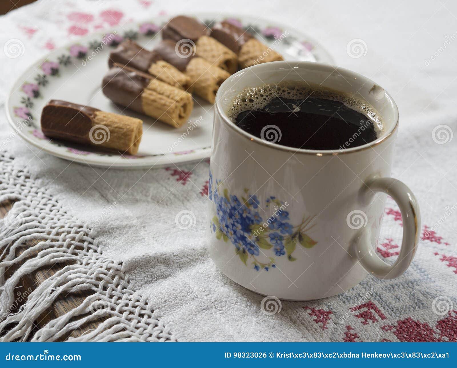 Den gamla kanstödda koppen med svart kaffe på lantlig bordduk med plat