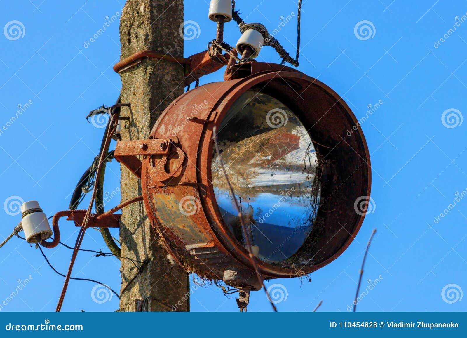Den gamla rostiga flodljuset monterade på en service av elektricitetsöverföringar