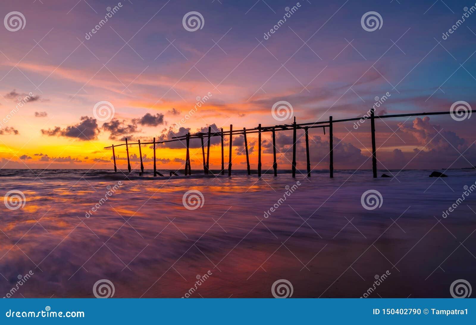 Den gamla träbro- och havsvågen på stranden på solnedgånghimmelbakgrund på Khao Pilai, Phangnga, Thailand ?pplet clouds treen f?r