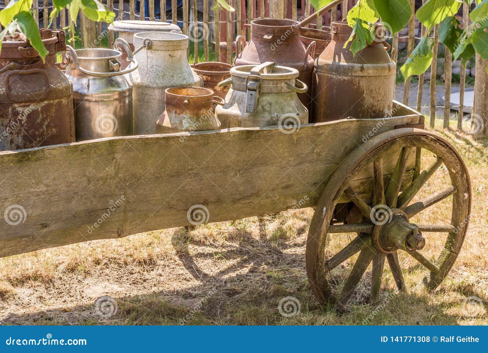 Den gamla vagnen med mjölkar mjölkkannor som laddas som en garnering på en lantgård